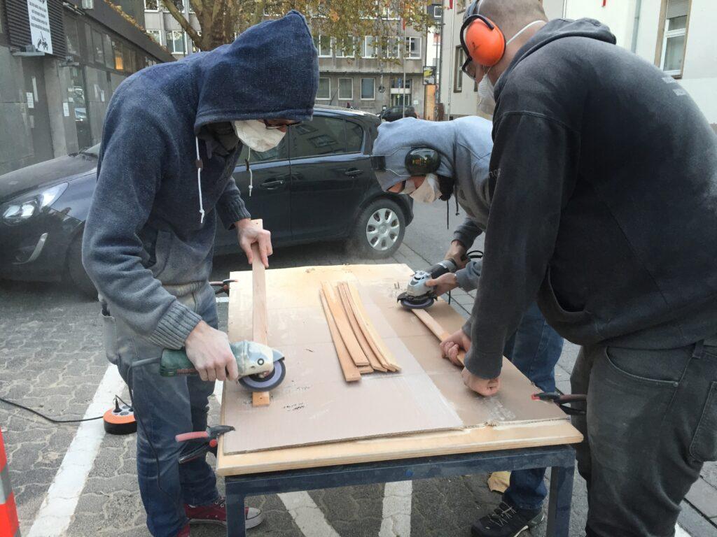 Menschen schleifen Holzlatten ab
